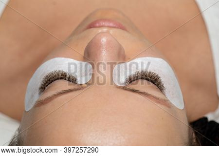 Woman closed eyes with Long Eyelashes Extension and eyepatch under eyes. False Lashes ater beauty treatment
