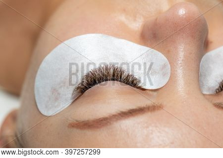 One Woman Eyes with Long Eyelashes Extension with eyepatch under eye after beauty treatment