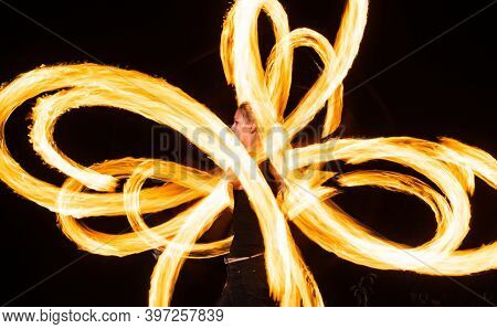 Sensual Woman Artist Perform Fiery Twirly Trails By Spinning Flaming Pois During Fire Performance In