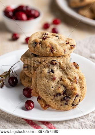 Stack Of Cranberry Walnut Cookies On A Plate With Bowl Of Cranberries In Background
