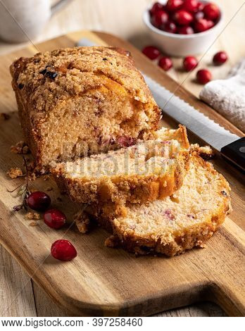 Cranberry Orange Sweet Bread Sliced On Wooden Cutting Board With Bowl Of Cranberries In Background