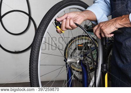 Bicycle Repair. Closeup. of a bike repairman pumping up a tire in his workshop.