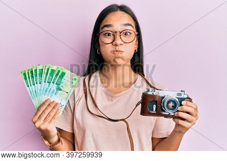 Young asian woman holding vintage camera and 200 russian ruble banknotes puffing cheeks with funny face. mouth inflated with air, catching air.