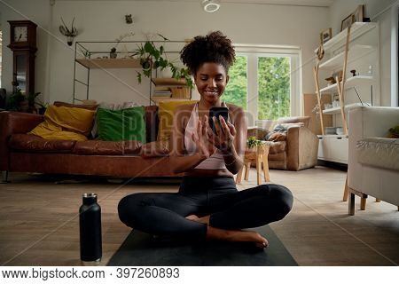 Portrait Of Smiling Young African Woman Using Smartphone After Routine Wokout With Bottle Besides At