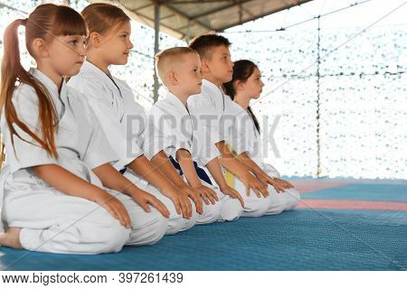 Children In Kimono Sitting On Tatami Outdoors. Karate Practice
