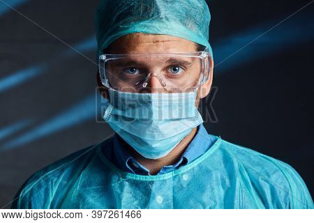 Portrait of tired good looking young doctor in protective medical face mask and glasses. Covid-19 virus prevention.