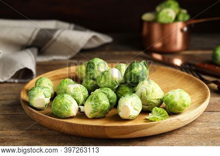 Plate With Fresh Brussels Sprouts On Wooden Table, Closeup