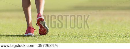 Runner Athlete Feet Running On Grass. Female Fitness Sunlight Jogging Workout. Sport Athlete Active