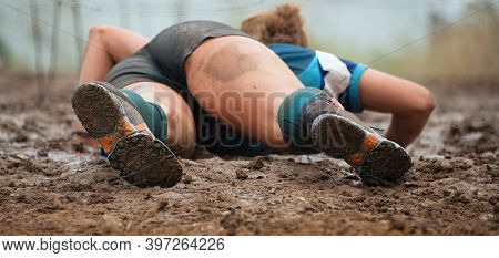 Mud Race Runners. Crawling, Passing Under A Barbed Wire Obstacles During Extreme Obstacle Race