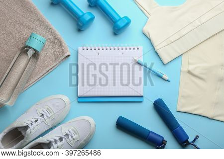 Flat Lay Composition With Sportswear, Notebook And Dumbbells On Light Blue Background, Space For Tex