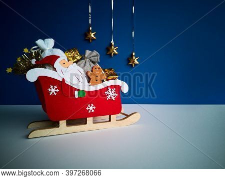 Christmas Gift Concept.santa Claus In Red Sleigh On Wooden Runners With Ginger,gray,white Sackfuls O
