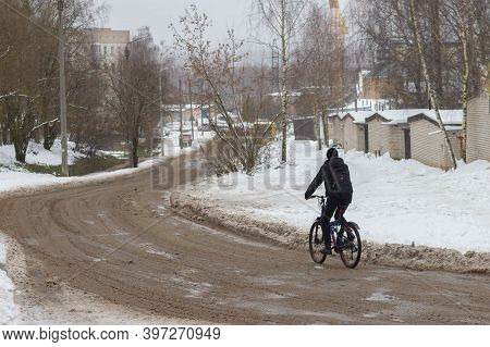 A Man Rides A Bicycle In Winter On A Muddy Road In Slush And Snow.