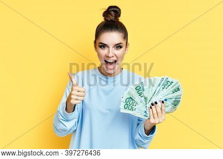 Happy Excited Young Woman Showing Money Banknotes With Thumbs Up On Yellow Background. Motivation, S