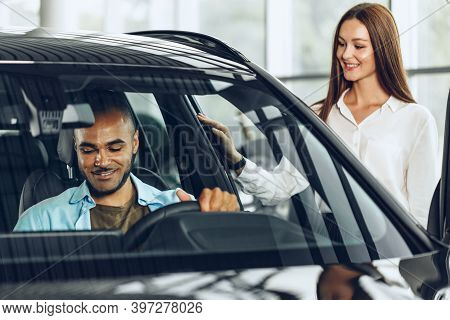 Young Woman Salesperson In Car Showroom Showing A Car To Her Male Client