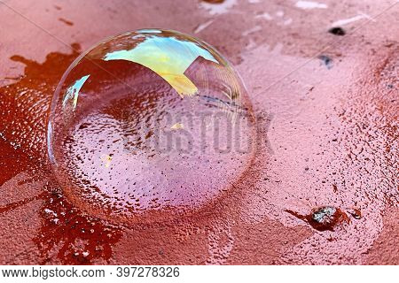 The Soap Bubble Lies On A Red Brick Surface. Transparent Soapy Surface With Rainbow Colors And Refle