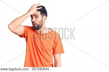 Young handsome man with beard wearing casual t-shirt surprised with hand on head for mistake, remember error. forgot, bad memory concept.
