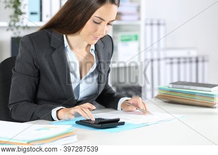 Bookkeeper Woman Calculates On Calculator Sitting On A Desk At The Office