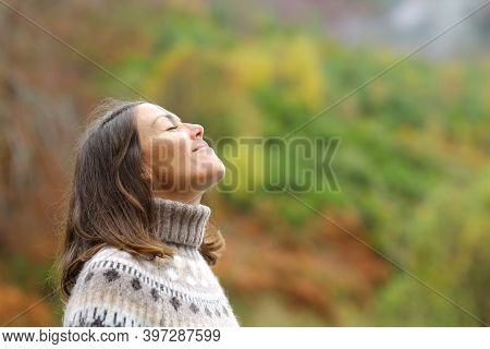 Side View Portrait Of A Middle Aged Woman Breathing Fresh Air In A Forest