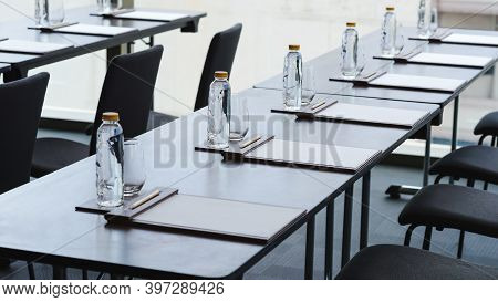 Plastic Water Bottles, Drinking Glasses With Pencil And White Papers Setup On The Table Prepared For