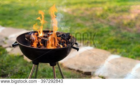 Burning Wood In Barbeque Grill, Preparing Hot Coals For Grilling Meat In The Back Yard. Shallow Dept