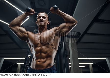 Caucasian Power Athletic Man Training Pumping Up Triceps Muscles. Strong Bodybuilder With Six Pack,