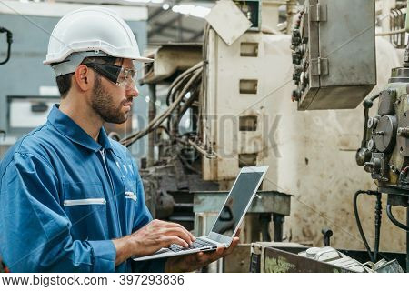 Factory Engineer Or Mechanical Worker Wearing White Safety Helmet Holding Laptop And Checking On Pro
