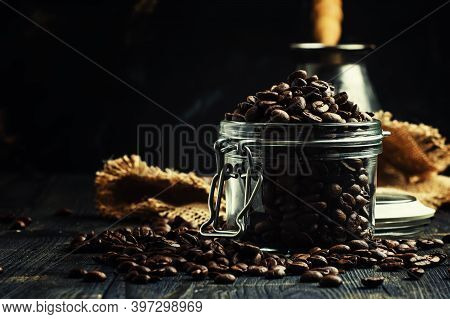 Grains Of Roasted Arabica Coffee In A Jar On Black Background, Selective Focus