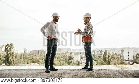Low Angle Side View Of Professional Foreman Discussing Work Plans With Engineer While Having Meeting