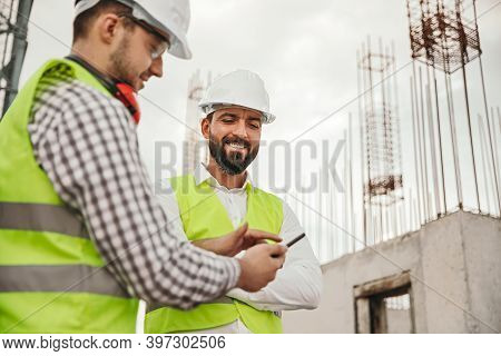 Low Angle Of Smiling Multiracial Male Coworkers In Hardhats And Waistcoats Using App On Mobile Phone