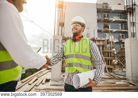 Positive Male Builder With Blueprint Shaking Hand Of Crop Partner While Standing Near Unfinished Bui