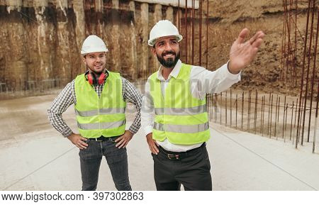Optimistic Diverse Male Coworkers In Hardhats And Waistcoats Standing On Foundation Of New Building