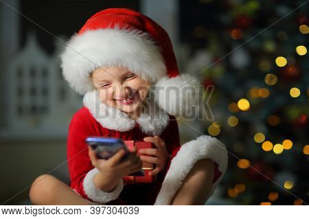 Child A Girl In A Bright Red Suit And Santa Hat Laughing Loudly Tells Friends On The Phone About A G