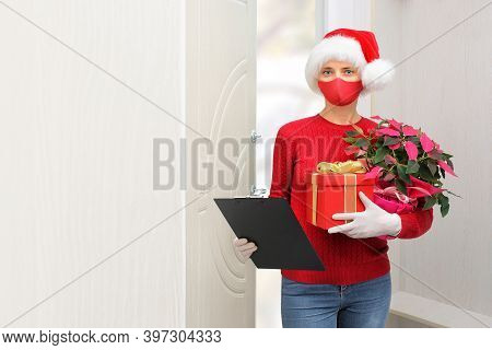 Home Shopping Delivery A Woman Wearing A Santa Claus Helper Hat, Gloves And A Protective Mask Delive