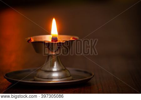 Close View Of Lit Diya Lamp. Lamp Made Out Of Silver Metal Lit During Festival.