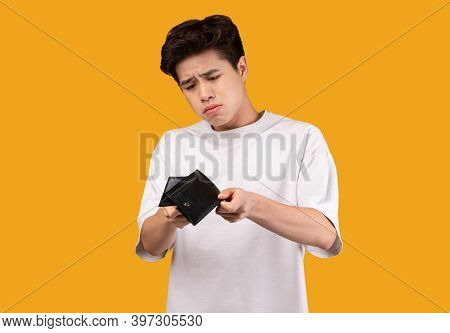 I Dont Have Money. Portrait Of Upset Asian Man Looking At His Empty Wallet. Depressed Sad Guy Standi