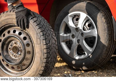 A Man Rolls A Wheel With A Studded Tire On The Background Of A Red Car With A Summer Tire. The Conce