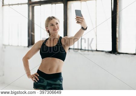 Fitness Blogger At Work And Workout At Home In Morning. Smiling Muscular Middle Aged Woman Coach Or