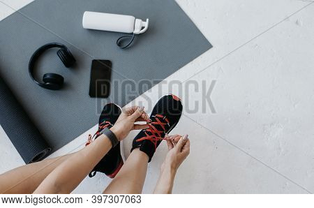 Modern Devices For Training, Indoor. Woman Athlete With Fitness Tracker Ties Shoelaces On Sneakers,