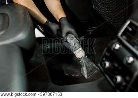 Details Of Car Vacuum Cleaning. Professional Male Worker Using Wet Vacuum Cleaner For Dirty Car Inte