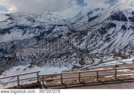 Grossglockner Alpine Road in Austria. Steep stone-paved bend. The roadside is fenced. The road consists of 36 serpentine turns. The first snow fell.  Ecological, active and photo tourism concept