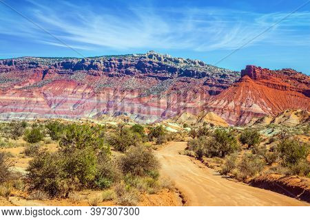 Red sandstone dirt road. Paria Canyon-Vermilion Cliffs Wilderness Area. Huge slopes of red sandstone, striped from various inclusions of light rocks. The concept of extreme and photo tourism