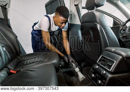 Handsome Young African American Man Auto Service Worker, Doing Professional Vacuum Cleaning Of Salon