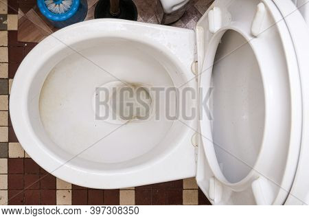 Dirty Unhygienic Toilet Bowl With Limescale Stain At Public Restroom, Top View.