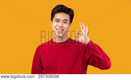 Everything Is Okay. Portrait Of Positive Smiling Asian Guy Doing Approval Ok Gesture With Fingers, S