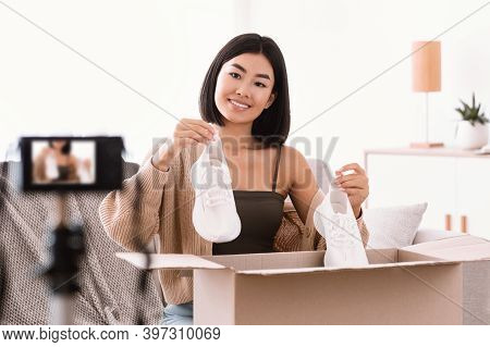 Ecommerce And Selling Online. Young Asian Woman Recording Video Blog With Camera, Holding And Showin