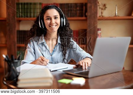 Telecommuting. Portrait Of Smiling Woman In Wireless Headset Sitting At Desk, Using Laptop And Writi