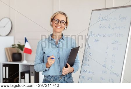 Friendly Young Female Tutor Standing Near Blackboard With French Grammar Rules, Giving Web Lesson Fr