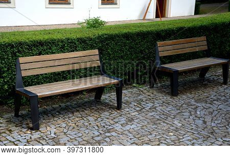 Park Benches In Front Of A Trimmed Hedge. The Benches Are Metal Modern With Wide Black Legs. The Woo