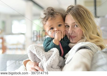 Portrait of young mom cuddling baby girl sitting in sofa
