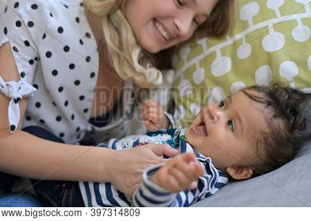Young mom tickling with baby girl